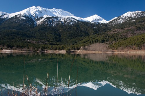 Doxa lake and mountain Helmos reflection on its calm water